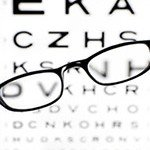 Eye exam chart with a pair of glasses sitting over it