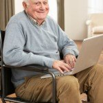 Older Man in a wheelchair using a laptop computer