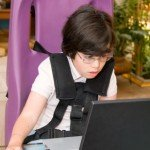 Young Girl with physical disabilities using a computer
